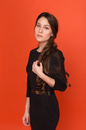 Beautiful young girl in a business suit on a red background in the studio Stock Photo