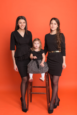 Two beautiful young girls in business suits and a little girl in a black dress on a red background in the studio 스톡 콘텐츠