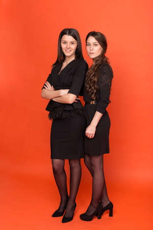 Two beautiful young women in business suits on a red background in studio 스톡 콘텐츠