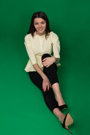 brightness: Beautiful brunette in a yellow blouse and black pants on a green background in the studio