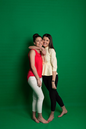 Two brunette girlfriends posing on green background in studio