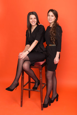 Two beautiful young women in business suits on a red background in studio 写真素材
