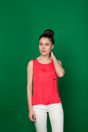 brightness: Beautiful young girl in a red blouse and white trousers on a green background in the studio