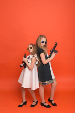 against the war: Two girls in military dresses with arms in hand and sunglasses on red background in studio