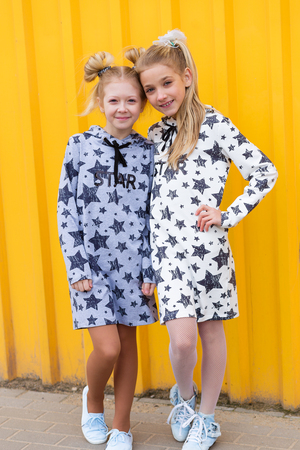 brightness: Portrait of girls on yellow background. Two sisters  against a yellow wall in the open air Stock Photo