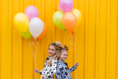 brightness: Portrait of girls with balloons on yellow background. Two sisters with gel balls against a yellow wall in the open air Stock Photo