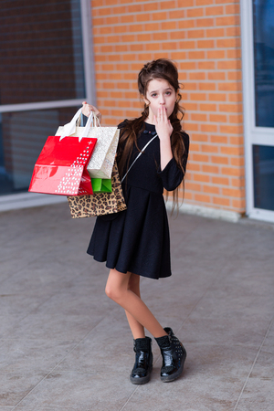 Beautiful young girl with a lot of packages at the outlet of the store. A child in sunglasses with shopping Stock Photo
