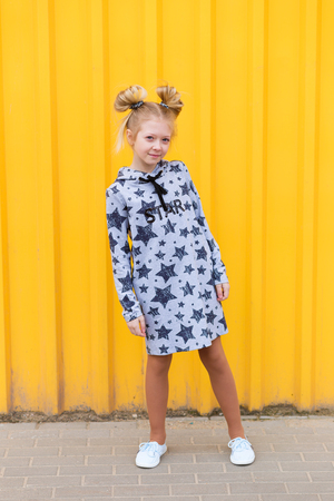 brightness: Portrait of a beautiful blonde girl on a yellow background outdoors in summer