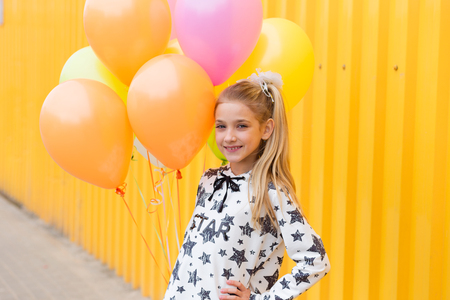brightness: Portrait of a beautiful blonde girl with gel colored balls on a yellow background outdoors in summer