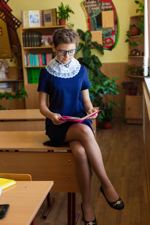 Girl at school desk. Child is sitting at school with books, notebooks and telephones. Child study in the school room. Selfie