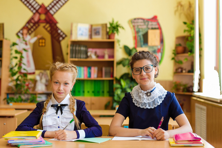 Girls at school desks. Girlfriends are sitting at school with books, notebooks and telephones. Children study in the school room Stock Photo