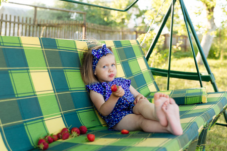 Porträt eines kleinen Mädchens essen eine Erdbeere. Das Mädchen freut sich in den Strahlen der untergehenden Sonne Standard-Bild - 84548136