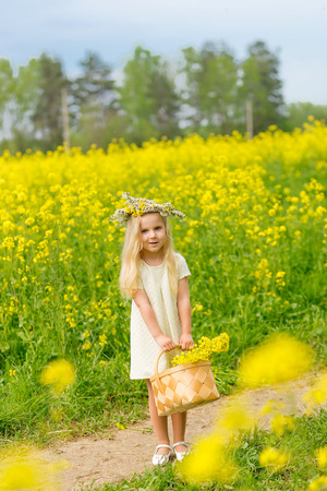 Beautiful little girl with a wreath on her head playing in a flowering field. A girl is playing in nature surrounded by yellow flowers. Young blonde with a basket with wildflowers