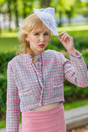 Portrait of a young blonde in a pink suit in a park outdoors. Vintage style