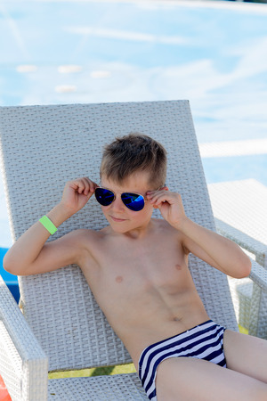 A young boy in sunglasses in a swimsuit on a shelf by the pool in summer