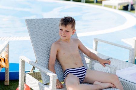 Young boy in a swimsuit on a shelf by the pool in summer Foto de archivo