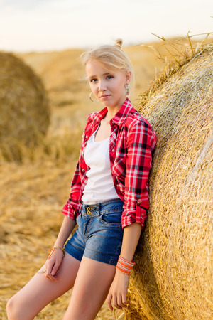 Young girl on straw sheaves in a field. Girl on a wheat field in the rays of the setting sun. Archivio Fotografico