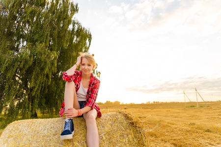 Young girl on straw sheaves in a field.