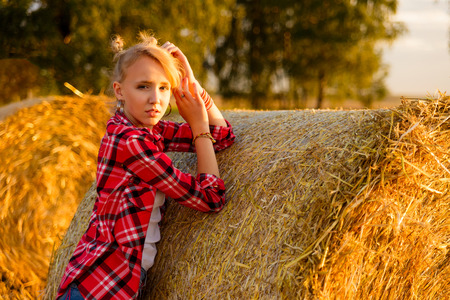Young girl on straw sheaves in a field. Girl on a wheat field in the rays of the setting sun. Stock Photo