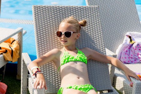 Young girl in a swimsuit on a shelf by the pool in summer Archivio Fotografico