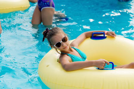 A young girl in the pool on an inflatable lap. The girl is swimming in the pool