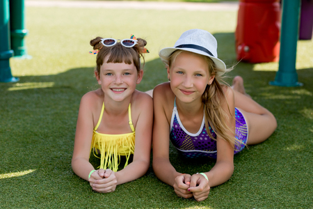 Two girls in swimsuit are having fun on the grass by the pool in summer Stock Photo