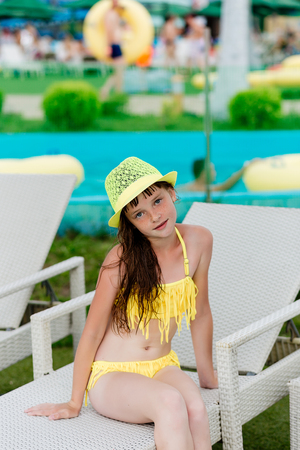 Young girl in a swimsuit on a shelf by the pool in summer Stock Photo