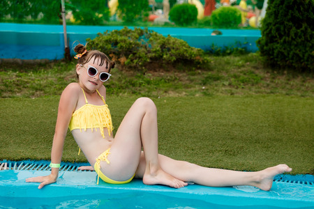 Beautiful girl in a swimsuit swims in the pool by the summer