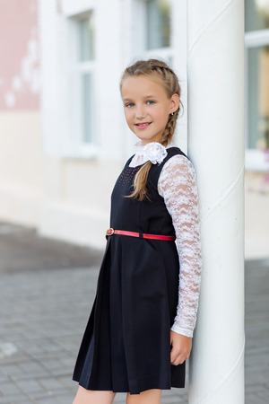 Portrait of a beautiful girl in a school uniform before class at school. School style