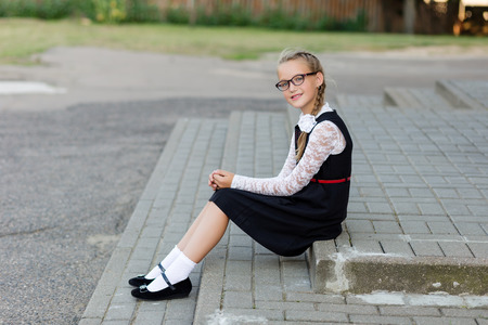 Young schoolgirl with glasses and school uniform outdoors in front of school. School style