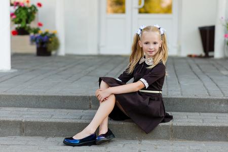 Portrait of a beautiful girl in a school uniform before class at school. School style