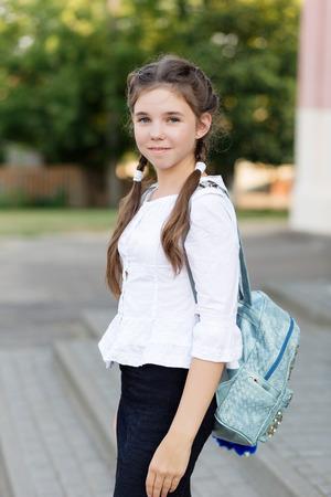 Beautiful schoolgirl in school uniform with a backpack at the school. School style Stockfoto