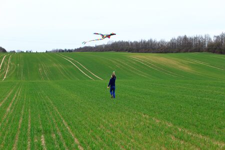 Boy launches a kite in a field in spring.