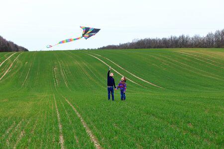 Children launch a kite in a field in spring