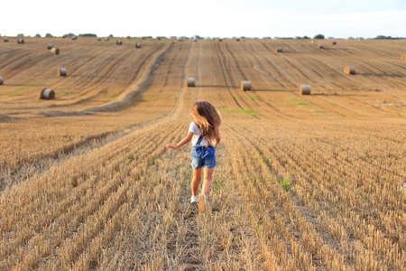 Girl runs on a mown field in summer