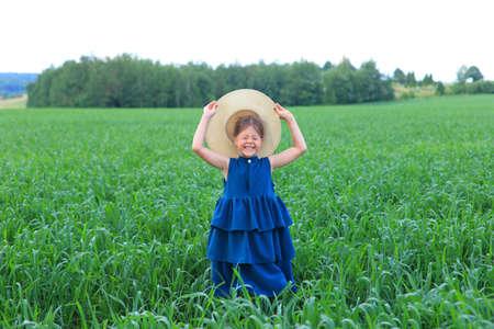 Beautiful little girl runs in the summer field