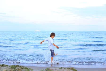 A boy runs on the water near the sea