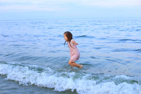 A barefoot child walks by the sea