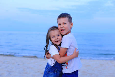Two children stand on the seashore in summer.