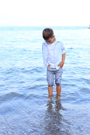 Beautiful boy stands on the seashore in summer. A child walks on the water near the shore Stockfoto