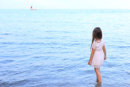 Cute girl stands on the seashore in summer