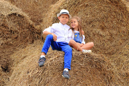 Two children are high under the sky on a haystack in the hay season.