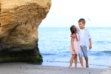 Two children stand on the seashore in summer
