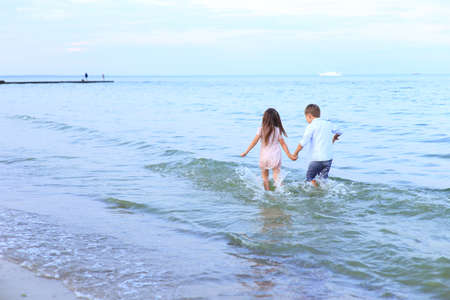 Two children run along the sea near the shore. Children hold hands and walk barefoot on the water