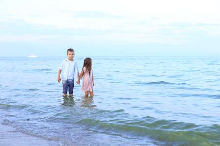 Two children run along the sea near the shore