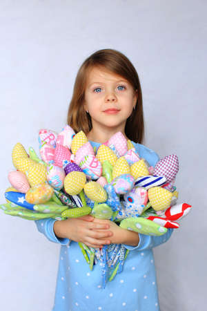 Beautiful blue-eyed girl stands with flowers in her hands