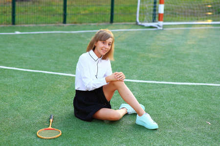 A girl in a school uniform with a racket in her hands on the football field.
