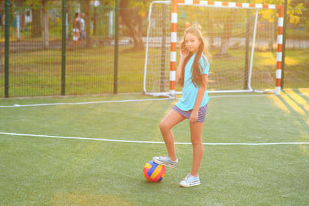 Girl with a ball in his hands on the football field.