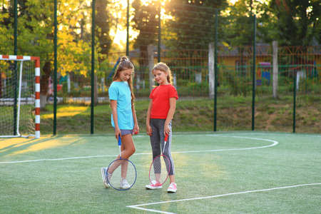 Two girls with badminton rackets on the football field.