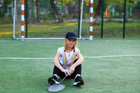Girl with a racket in her hands on the sports field.